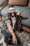 Joyful happy man enjoying his phone conversation royalty free stock images