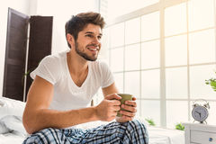 This is wonderful morning. There is no place like home. Carefree young man is drinking coffee and dreaming. He is sitting on bed and smiling Stock Image