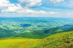 Wonderful mountain landscape in summer. Green grassy hills and slopes. path downhill through the meadow. settlement and rural area in the distant valley royalty free stock photos