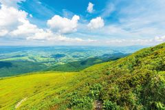 Wonderful mountain landscape in summer. Green grassy hills and slopes. path downhill through the meadow. settlement and rural area in the distant valley stock images