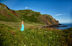 Beautiful blonde woman in turquoise green long dress, stands in the middle of a field, close to the sea, in Ireland. royalty free stock photography