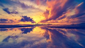 Orange pink and purple evening clouds reflected in sea. Wonderful orange pink purple evening clouds in endless sky reflect in tranquil ocean against hills at stock video