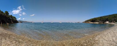 Panorama of Malpasso. On Elba Island, Italy. Wonderful panorama of Malpasso beach. White boats on the background of the blue sky. Colored pebbles in crystal royalty free stock photo