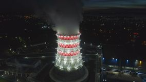 Panoramic view modern cooling tower with steam against city. Wonderful panoramic view modern red and white cooling tower with rising steam and large city in dark stock video