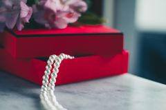 Wonderful pearls in a red gift box, luxe present - jewellery and luxury gift for her styled concept. Elegant visuals stock photography