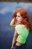 A wonderful portrait of a beautiful red-haired girl brought in a. Green blouse and jeans on a background of lake, side view Royalty Free Stock Images