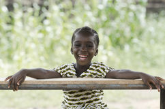 Wonderful portrait of little African girl. Little african girl sitting at wooden table and smiling at camera with blurred background Stock Images