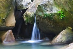 Wonderful refreshing waterfall among the rocks of mountain creek. Wonderful refreshing waterfall among the rocks of the mountain creek royalty free stock photography