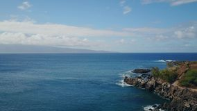 Blue waters of pacific ocean and rocky shore under blue sky with clouds on island maui,hawaii stock footage