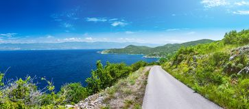 Wonderful romantic summer afternoon landscape panorama coastline Adriatic sea. A narrow mountain road above the cliffs along the c Stock Images