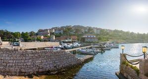 Wonderful romantic summer evening landscape marine in backlit su. Nset sunbeam panorama at coastline Adriatic sea. Fishing boats and yachts in harbor. Mali Stock Photography
