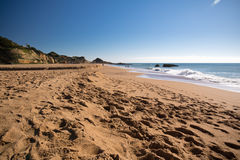 Wonderful sandy beach in abufeira with breaking waves. Relaxing on beautiful sandy beach in blue sky of albufeira, algarve, portugal royalty free stock photography