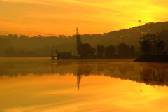 Da Lat sunrise, Thuy Ta restaurant. Wonderful scenery of Da Lat city at sunrise, Thuy Ta restaurant reflect on water, yellow sky and lake in fog make romantic stock photos