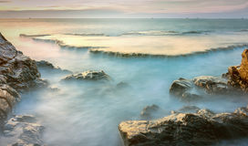 Wonderful seascape with sea waves hitting large rock. Formed soft sheet like a cascade of water floating in the morning to greet the new day Royalty Free Stock Photos