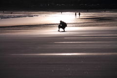 Wonderful silhouette of people walking on sandy beach in colorful sunrise summer sky with reflection. In black and white effect, hendaye, basque country, france Royalty Free Stock Photography