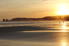 Wonderful silhouette of people walking on sandy beach in colorful sunrise summer sky with reflection Stock Photography