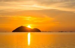 GOLDEN SKYLIGHT SUNSET TIME HIDEN BEHIND ISLAND royalty free stock photo
