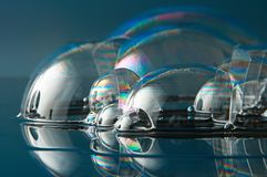 Wonderful soap. Soap bubbles and their colors on a reflective surface stock image
