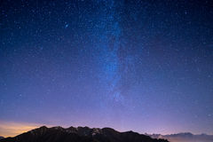 The wonderful starry sky on Christmas time and the majestic high mountain range of the Italian French Alps, with glowing villages Royalty Free Stock Image