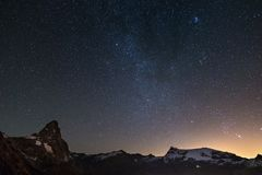 Wonderful starry sky over Matterhorn Cervino mountain peak and Monte Rosa glaciers, famous ski resort in Aosta Valley, Italy. An. Dromeda galaxy clearly visibile Stock Image