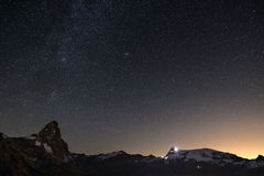 Wonderful starry sky over Matterhorn Cervino mountain peak and Monte Rosa glaciers, famous ski resort in Aosta Valley, Italy. An. Dromeda galaxy clearly visibile Royalty Free Stock Photography
