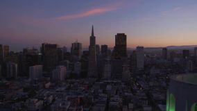 Wonderful steady aerial view on real time big San Francisco warm pink blue evening sunset cityscape downtown silhouette stock video footage