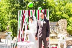 Wonderful stylish rich happy bride and groom at a wedding ceremony in green garden near wedding arch stock photos