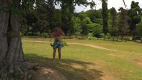 Wooden swinging tied to tree. Male swinging on swing with bare feet forward. Wonderful summer nature landscape. View green lawn surrounded by tree. Wooden stock video