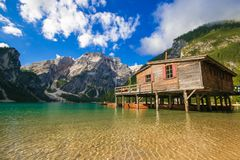 Wonderful summer scenery of Braies Lake Pragser Wildsee with wooden hut on shore and colorful trees and mountains on background royalty free stock photography