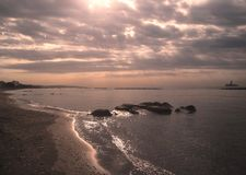 Wonderful sunrise over the sea, cloudy sky and glitter wave Royalty Free Stock Photography