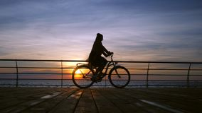 Wonderful sunrise or sunset above ocean. Silhouette of young stylish girl cycling on vintage bike on wooden embankment stock video footage