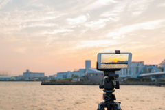 Wonderful sunset over sea harbor, tourist taking a picture by tr Stock Image