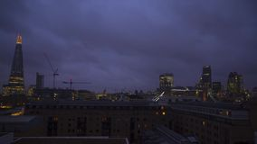 Wonderful time lapse steady shot of heavy rain clouds moving fast in dark night sky over modern downtown London rooftops. Modern London downtown in time lapse stock video