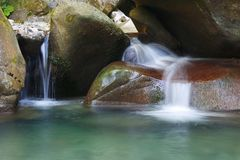 Wonderful tranquil waterfall among the rocks of mountain creek. Wonderful tranquil waterfall among the rocks of the mountain creek stock photo