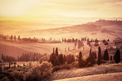 Wonderful Tuscany landscape with cypress trees, farms and small medieval towns, Italy. Vintage sunset Royalty Free Stock Photos