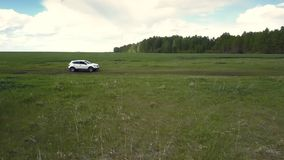 Upper view auto drives along ground track among fields stock video