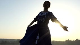 A beautiful woman flutters her folk dress at sunset in 4k stock video footage