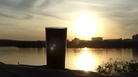 A plastic cup of coffee on a lake bank at a nice sunset in Ukraine. A wonderful view of a plastic cup of hot coffee on a picturesque lake bank at a splendid stock video