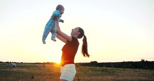 Emotional young woman raising her baby in hands in a field at sunset in slo-mo royalty free stock images