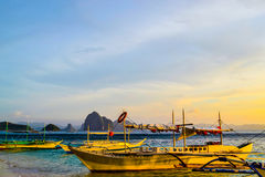 Wonderful view of the sunset sky shimmering sea cliffs on the horizon and the boats moored next to a sandy beach. Royalty Free Stock Photo