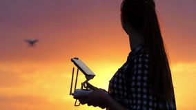 Clever woman controls a panel to operate a drone at sunset. A wonderful view of a young woman who works with a panel with a screen to control a flying drone at a stock footage