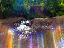 Wonderful waterfall with rainbows in deep forest. Small waterfall in the forest with a rainbow Stock Image
