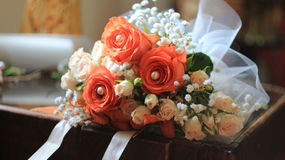 Wonderful wedding bouquet with orange roses,lilies,pearls,white tulle and decorative ribbon Stock Photography