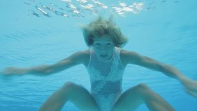 Wonderful woman in a white lace swimsuit swims underwater in a swimming pool. Young blonde girl,dressed in a white one piece lace swimsuit, swims breaststroke stock video