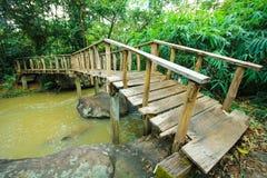 Wonderful wooden bridge across a waterfall, Thailand Stock Photo