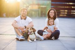 Wonderful young family is resting sitting on the ground. Dad, Mom, little daughter and beagle. Warm summer weather, good mood royalty free stock photo
