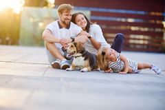 Wonderful young family is resting sitting on the ground. Dad, Mom, little daughter and beagle. Warm summer weather, good mood stock photos