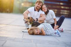 Wonderful young family is resting sitting on the ground. Dad, Mom, little daughter and beagle. Warm summer weather, good mood royalty free stock images