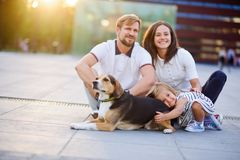 Wonderful young family is resting sitting on the ground. Dad, Mom, little daughter and beagle. Warm summer weather, good mood stock images