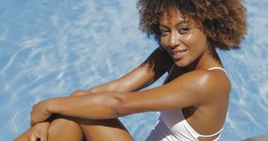 Wonderful young girl in pool. Portrait of young curly ethnic model in white swimsuit sitting on poolside relaxing and smiling at camera happily Royalty Free Stock Images